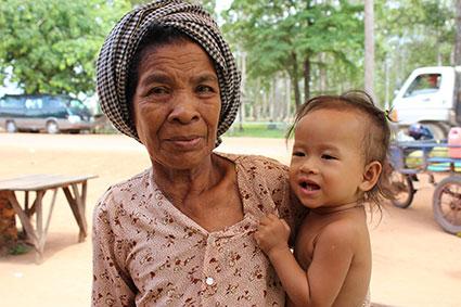Una mujer sostiene en brazos un niño en una zona de puestos de comida de carretera, cerca del complejo de Angkor (Camboya).