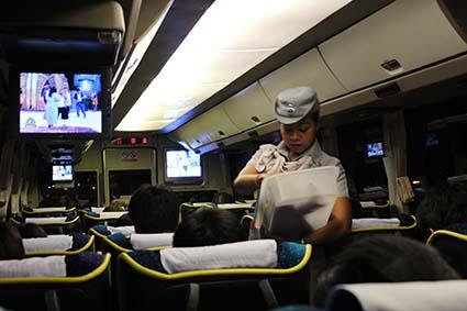 La azafata del autobús Gold Class que nos llevó de Chiang Mai a Bangkok reparte snacks a los pasajeros (Tailandia).