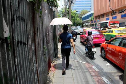 Una bangkokí se protege del sol con un paraguas en una calle de Bangkok.