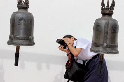 Una escolar fotografía una de las campanas del Golden Mountain, en Bangkok.