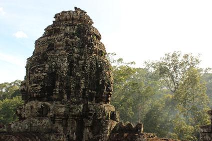 La luz se cuela por entre los árboles de la selva para iluminar el templo de Smiling buda, en Camboya.