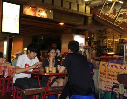 Cena en el puesto callejero bajo los andenes de la parada Siam del Sky Train, en Bangkok.