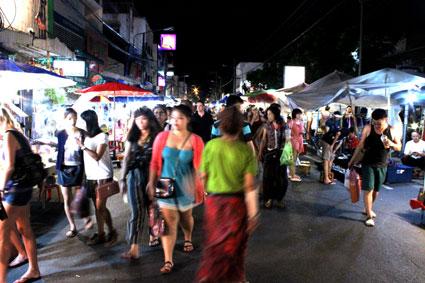 """Decenas de """"farangs"""" o extranjeros se detienen en los centenares de puestos callejeros del Sunday Walking Street, en Chiang Mai."""