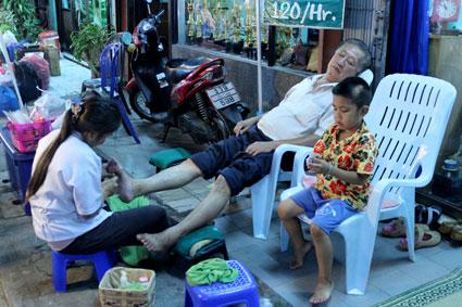 Uno de los varios puestos callejeros donde tomar un masaje tailandés en pies y piernas, en el Saturday Walking Street, Chiang Mai.