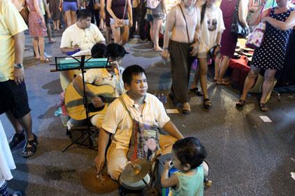 Un grupo de invidentes sentados en plena calle tocan y cantan durante el mercado callejero del Saturday Walking Street, (Chiang Mai).