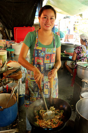 La cocinera de un puesto preparándo un plato de noodels mixto, en el mercado de Tha Chang (Bangkok).