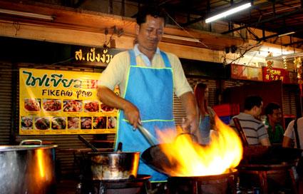 Un cocinero preparando un plato al estilo wok en China Town, Bangkok.