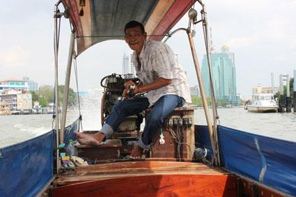 Conductor de uno de los centenares de botes que cada día surcan las aguas del Chao Praya, en Bangkok.