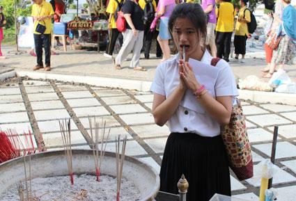 Una escolar reza después de haber encendido varias barritas de incienso en Wat Arun, Bangkok.
