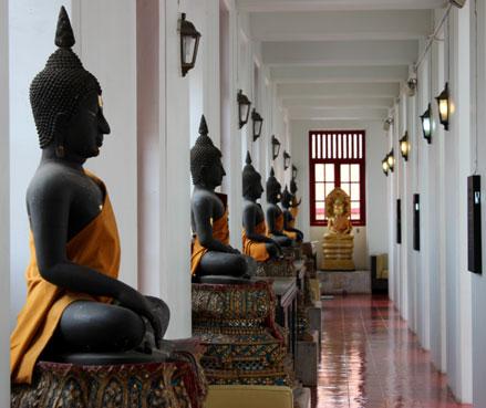 Varias estatuas de buda en uno de los pasillos del Loha Prasat, Bangkok.
