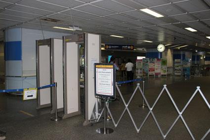 Arco de seguridad de la parada de metro de Sala Daeng. Un policía registra bolsas y mochilas de los usuarios (Bangkok).