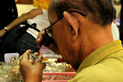 Un tailandés observa detenidamente los detalles de un amuleto de buda contemplativo, en el mercado de amuletos (Bangkok).