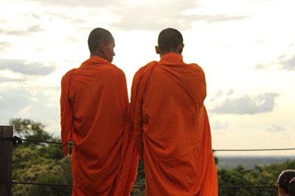 Dos monjes budistas observar el atardecer desde lo alto del templo