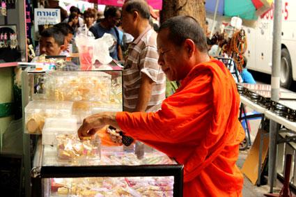 Un monje budista mira en uno de los puestos del mercado de amuletos en Bangkok.
