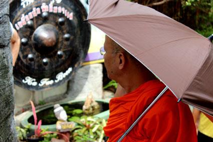 """Un monge budista observa uno de los """"dongs"""" en el Golden Mountain, Bangkok."""
