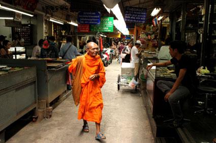 Un monje recorre los puestos del mercado de amuletos en Bangkok.