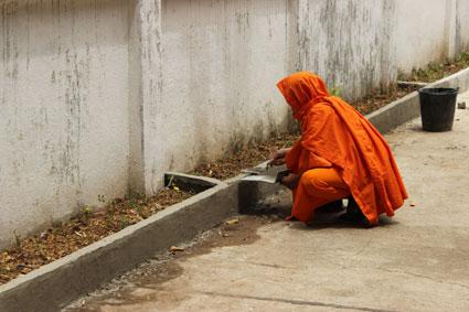 Un monje budista arregla la fachada de un templo en Pai, al norte de Tailandia.