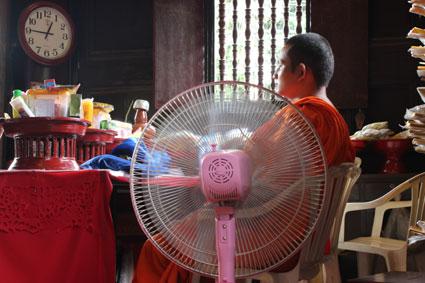 Un monje budista se refresca con un ventilador en un templo en Chiang Mai, Tailandia.