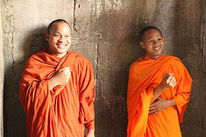 Dos monjes se golpean el pecho con el puño derecho y consiguen que los golpes resuenen en una de las cámaras de Angkor Wat (Camboya).