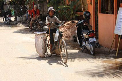 Una niña transporta dos grandes sacos de deshechos reciclables a bordo de su bicicleta, en una calle de Siem Reap (Camboya).