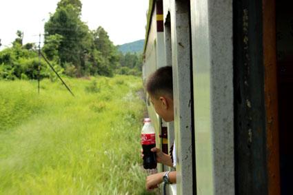 Un joven tailandés observa el paisaje desde el tren de Bangkok a Chiang Mai.