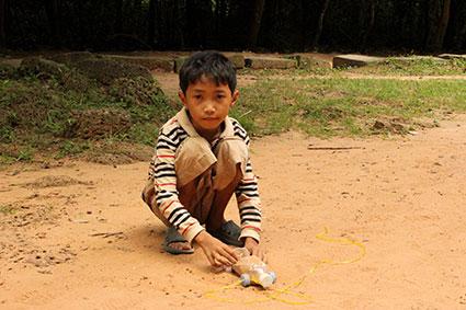 Un niño juega con un coche hecho con una botella de plástico entre los templos de Angkor Wat (Camboya).