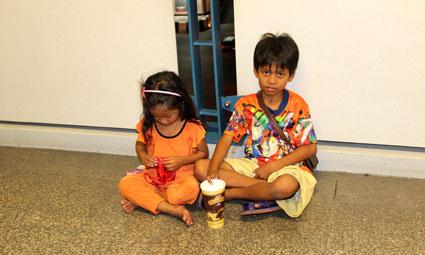 Dos hermanos mendigano en la estación del Skytrain de Siam, en Bangkok