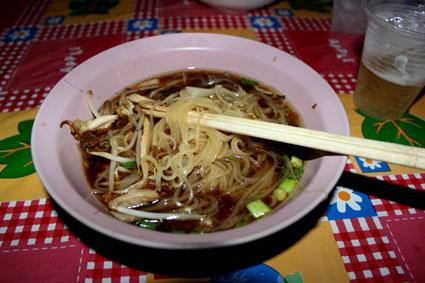 Delicioso plato servido en un puesto callejero bajo los andenes de Siam SkyTrain, Bangkok.