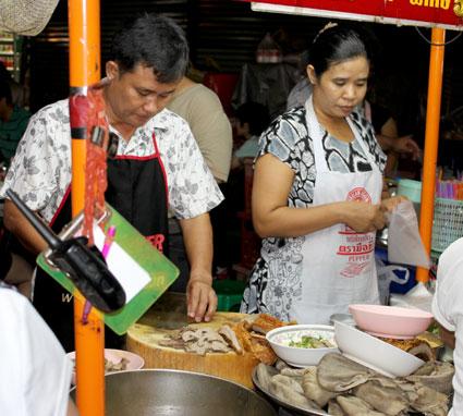 Cortando tiras de cerdo crujiente para llevar en un puesto de China Town (Bangkok).