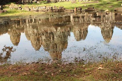 El reflejo del templo Bayón o Angkor Thom en un pequeño charco de agua en Angkor Wat (Camboya).