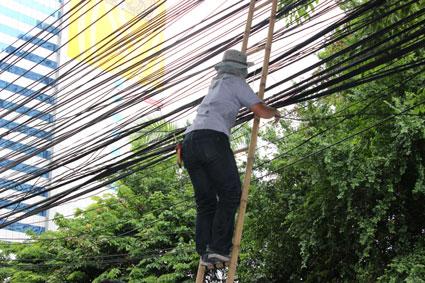 Un operario repara el tendido eléctrico, sujetado por una escalera de bambú, en plena calle de Bangkok.