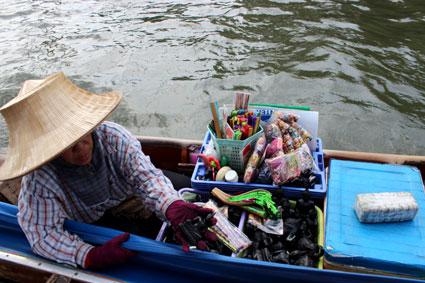 Una vendedora ambulante abordo de su embarcación ofrece una estatuilla a los turista, en pleo río Chao Praya, Bangkok.