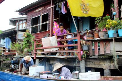 Una vendedora de un puesto ambulante prepara unas brochetas a la brasa, mientras una familia de la ribera espera su comanda, (Bangkok)