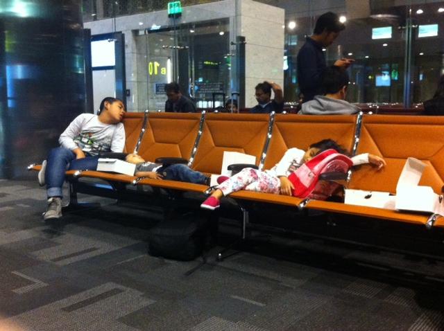 Algunos niños caen rendidos en el aeropuerto de Doha (Qatar) durante el retraso del vuelo hacia Yakarta (Indonesia).
