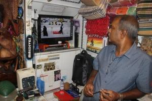 El dependiente de la tienda de souvenirs mira entretenido el partido de este particular deporte en la pantalla de su televisión, Malé (Maldivas)