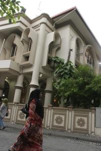 Una mujer camina frente a una de las mezquitas de Malé, Maldivas