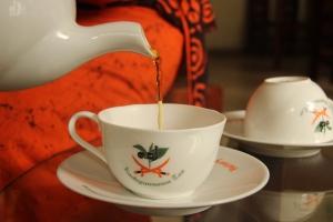 Nimesha sirve té negro en una taza vestida con el traje tradicional de Sri Lanka, en la Kadugannawa Tea Factory, Sri Lanka.