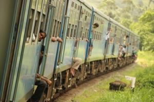 Los viajeros sacan brazos y cabezas a través de ventanillas y puertas para respirar el aire fresco y limpio, al paso del tren que va de Kandy a Ella, Sri Lanka