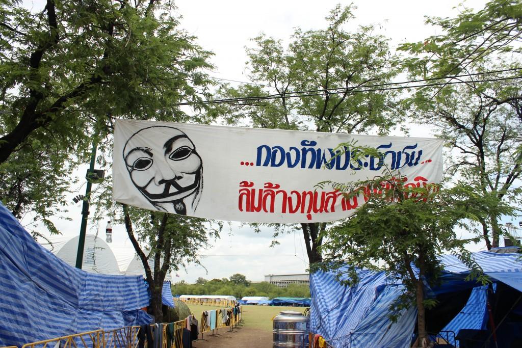 """Indignados organizados por el colectivo auto denominado """"V for Thailand"""" protestan para echar del gobierno a la primera ministra Yingluck Shinawatra, líder del partido Puea Thai, en el parque de Sanam Luang, Bangkok. (Foto tomada durante un viaje a Tailandia y Camboya en 2013). Autor: Diego Sánchez"""